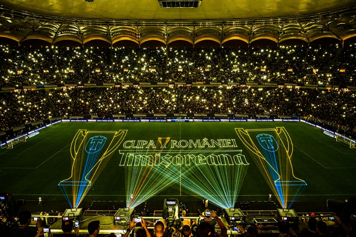"""Grossprojektionen beim """"Cupa Romaniei"""" in der National-Arena, Bukarest Es war eine grandiose Halbzeitshow die mit Lasergrafikprojektionen auf dem gesamten Spielfeld das Livepublikum und die Zuschauer vor den Bildschirmen begeistern konnte.  Vier vollfarbige tarm-Lasersysteme mit einer Ausgangsleistung von über 100 Watt überzeugten durch ein atemberaubendes Strahlprofil und kraftvolle Farben.  Der rumänische Fussballverband hat bereits einige Erfahrung mit dem Einsatz von Lasersystemen und greift immer wieder gerne auf die Dienstleistung der tarm Showlaser GmbH zurück. Neben einer Vielzahl von Produktionen in Rumänien, unterstützte damit das Unternehmen zum fünften Mal erfolgreich die Halftime Show des """"Cupa Romaniei""""."""