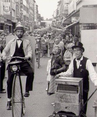 Nostalgiewerbung mit Hochradfahrer und Drehorgelspieler anlässlich einer Geschäftseröffnung