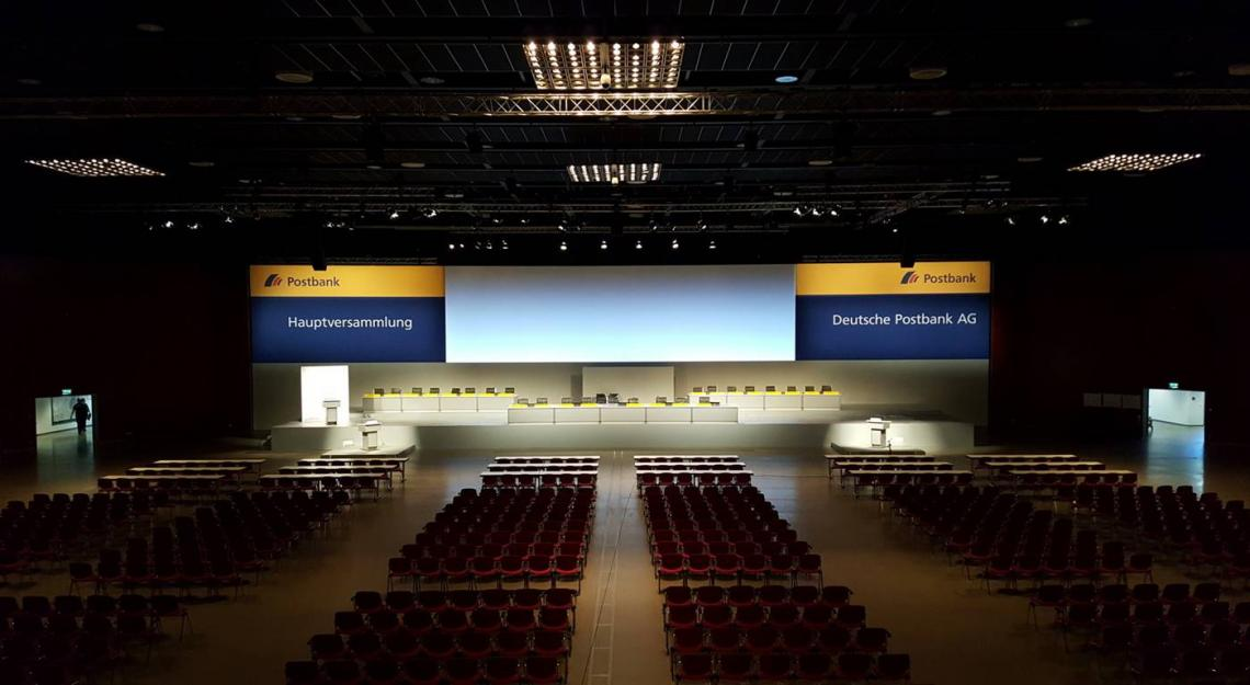Hauptversammlung Deutsche Post AG Die Postbank Hauptversammlung fand im Ruhrcongress Bochum statt. DEKO-Service setzte das komplette Bühnenbild, sowie über 120 lfm Raumbau um.
