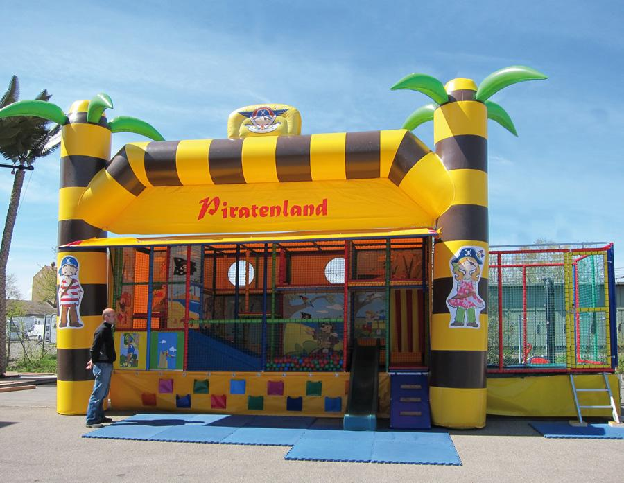 ERTL Karussell Land GmbH - Spielmobil Piratenland  Tretet ein ins Abenteuerland der Piraten! Das Spielmobil ist ideal geeignet für die Kleinen bei Ihrer Feier. Auf 3 Ebenen können sich die Kids beim Rutschen, Klettern und Spielen so richtig austoben. Zusätzlich ist hinten noch ein rundum vernetztes Trampolin angebracht mit separatem Ein- und Ausgang. Mit der freundlichen Palmendeko ein echter Hingucker der nicht nur die Kinder begeistert!