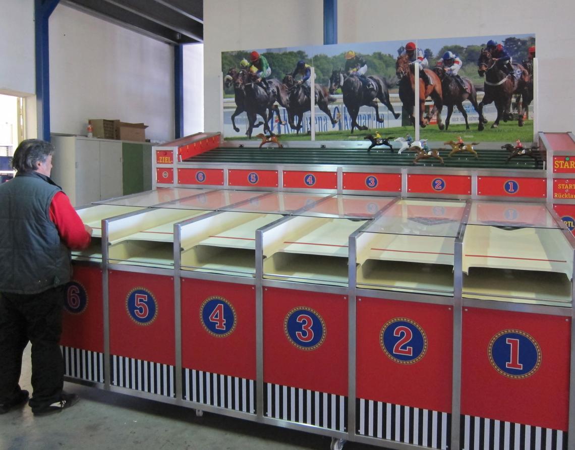 ERTL Karussell Land GmbH - Pferdederby Dieses Spiel kennt mit Sicherheit jeder von Jahrmärkten oder der Kirmes. Sie betreiben selbst einen Kirmesstand oder haben es vor? Dann schlagen Sie zu! Und auch auf jeder anderen Veranstaltung können Sie mit dem bekannten Pferdederby punkten. Ziel hierbei ist es, durch geschicktes Spiel mit der Kugel das eigene Pferd in Front zu bringen. Diesen Simualtor gibt es auch als Camelrennen, F1-Rennen oder Rad-Rennen.