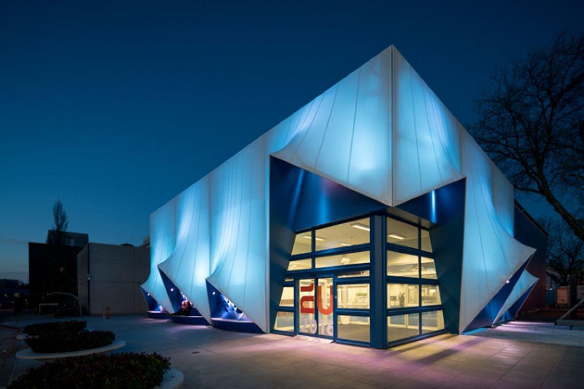 """Gebäude von Neptunus als Tagungszentrum für die EU–Ratspräsidentschaft der Niederlande Das demontierbare """"Europa-Haus"""" besteht aus sechs temporären Hightech-Gebäuden mit Konferenzräumen, Lounges, einem Theater, Dolmetscherkabinen und Räumen für Meetings. Ein eindrucksvolles, maßgeschneidertes 150 m2 großes Atrium unter der höchsten Spitze des Daches mit voll verglasten Wänden bildet einen Garten- bzw. Hofbereich. Die Außenwände sind verziert mit Fassadendekorationen und mit im 3D-Drucker hergestellten Bänken. Das Innere trägt eine typisch holländische Handschrift, fast museumsartig, mit Scheindecken, teilweise mit aufgedruckten Wolken dekoriert.  Trotz der Natur des Komplexes werden die meisten Besucher nicht merken, dass sie sich in einem temporären Gebäude befinden. Die Techniker von Neptunus benötigten nicht mehr als drei Monate für den Bau des Tagungszentrums, das im Inneren von drei ultramodernen und energieeffizienten temporären Evolution-Gebäuden, die durch überdachte Korridore verbunden sind, errichtet wurde."""