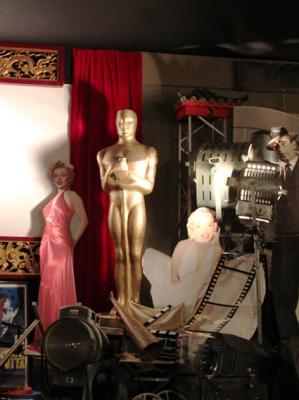 Filmrequisiten und Oscarstatuen Wir verleihen die unterschiedlichsten Requisiten und Ausstattungsstücke zum Thema Film und Hollywood. Darunter befinden sich u.a. alte Filmschweinwerfer, Kinositze, Filmdosen, Filmklappen, Regiestühle, Aufsteller, etc. Highlight des Fundus sind zwei große Oscar Statuen.