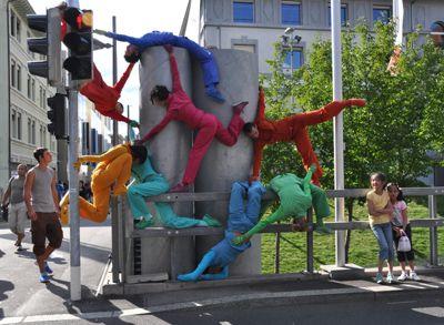 """DA MOTUS! (CH-Fribourg), Tanz-Performance für den öffentlichen Raum '…con tatto' Die Künstler aus Fribourg in der Schweiz pflegen einen eher instinktiven und sensoriellen Zugang zum Tanz. Mit ihren verschiedenartigen Produktionen wurde DA MOTUS! im Rahmen von internationalen Festivals und anderen, wichtigen kulturellen Anlässen in mehr als 150 Städten von 38 Ländern eingeladen. Ihre choreographischen Stadtinterventionen, Tanz-Performances für den öffentlichen Raum, werden weltweit geschätzt.  Mit """"…con tatto"""" präsentiert DA MOTUS ! eine feinfühlige Begegnung mit dem Publikum, in welcher sich ineinander verschlingende Tänzer mit Stadtarchitektur, Zuschauern und Passanten in Wechselbeziehung geraten. Einfühlsam und offenherzig  reagiert  """"...con tatto"""" gegen die wachsende Stimmung aus Misstrauen und Furcht, die sich vor allem in städtischer Umgebung ausbreitet. Es geht darum, den Kontakt anzuregen, den Austausch zu fördern und das Publikum einzuladen, an der Bewegung Gefallen zu finden.   Das Stück soll somit den Zauber einer wechselseitigen Wahrnehmung sowie den Charme einer sensiblen Verständigung erleben lassen - natürlich … mit Takt.  """"… con tatto"""" ist eine open-air Tanzperformance, die grundsätzlich in zwei Teile gegliedert ist: einen mobilen und einen fixen, """"bühnenähnlichen""""."""