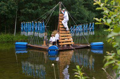 """VISUAL SOUND ART (NL-Amsterdam); 'Whistling Raft – pfeifendes Floß' Die Kreativität und Phantasien der holländischen Aktionskünstler scheint grenzenlos zu sein. Ob im Orient, Asien oder Skandinavien, Martien Groeneveld spielt virtuos auf selbstgebauten Instrumenten und Klangkörpern aus Alltagsgegenständen.  Auf einem  """"pfeifenden Floß"""" zaubern die holländischen Künstler mit """"Whistling Raft"""", eine außergewöhnliche Stimmung in die Landschaft. Das Floß ist auf beiden Seiten bestückt mit je 21 Wasserflöten, einem Riesenxylophon und mit Instrumenten aus dem indonesischen Gamelan-Orchester wie Gong, Anklung und Templi.  Magische Momente, Poesie und traumhaft schöne Klangbilder verändern den öffentlichen Raum und lassen ihn für die Menschen neu erfahrbar werden.  Die Vorstellungen können auch in der Dunkelheit gespielt werden, dann wird das Floß mit Fackeln beleuchtet und verbreitet zusätzlich eine romantische, mystische und magische Atmosphäre.  2 Tage Aufbau, 1 Tag Abbau, 2 Tage á 3 Vorstellungen (je 30 Minuten)"""