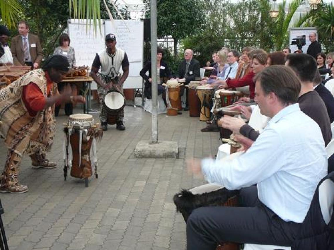 """Corporate Drumming und interaktive Trommelshows mit African Power Corporate Drumming mit afrikanischen Trommlern der Band """"AFRICAN POWER""""   Seit Jahrtausenden verwenden viele Kulturen Trommeln, um Menschen zu besonderen Anlässen zu vereine. Trommeln und Percussion-Instrumente sind ideale Mittel zur Teambildung und Kommunikation. Neben großer Aufmerksamkeit fördert die Trommel den Stressabbau, die Zusammenarbeit, den Informationsaustausch und liefert Einblicke in die Arbeitsweise von Gruppen.  Hören, sehen und fühlen Sie, wie der eigene Beitrag die Gruppe beeinflusst und wie die Energie der gesamten Gruppe ihre Leistung bestimmt.  Als einzigartige Methode des Event-Highlights bringen wir diese in Konferenzen, Messen und Firmenveranstaltungen ein.  Jeder Gast erhält eine afrikanische Trommel oder ein anderes Instrument und wir zeigen ihm die grundlegende Spieltechnik und die Wichtigkeit aufeinander zu hören, um in einer außergewöhnlichen und einzigartigen Erfahrung, durch Einheit und Teamgeist, ein Konzert mitreißender Musik zu entwickeln."""