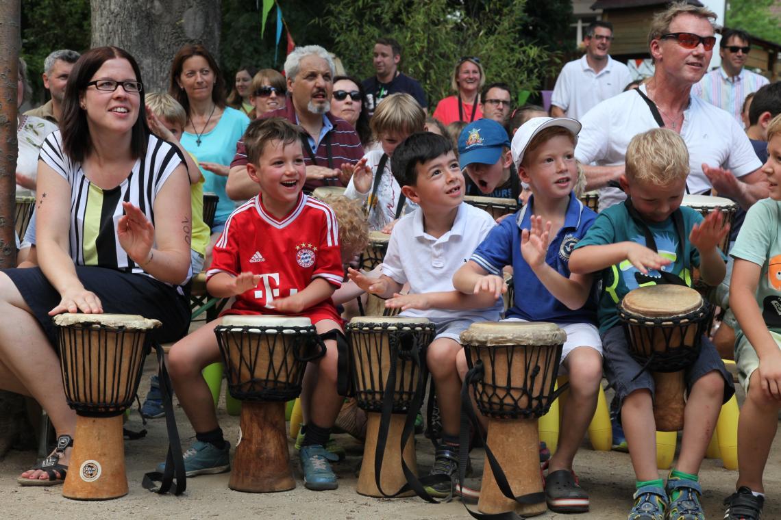 Sommerfest outdoor Jubiläum eines Kindergartens Familien trommeln gemeinsam.