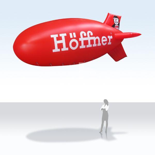 Werbezeppelin / Werbeluftschiff / Heliumzeppelin Höffner  Fliegende Werbung fällt auf ! Was kann es schöneres geben als von weitem auf sich mit einem Heliumzeppelin aufmerksam zu machen. Der Anfertigung und Druck erfolgt nach Kundenwunsch. Die Formen reichen von einfachen Riesenballonen über Zeppeline bis zu Maskottchen und Produktnachbildungen. Rufen Sie uns an - wir beraten Sie gerne !