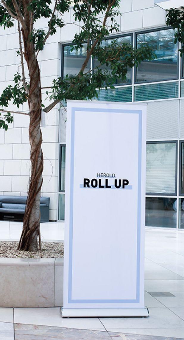 Roll Up Luxury Hochwertig, auswechselbar! Die Verarbeitung des Roll-Up-Luxury ist durchweg erstklassig und überzeugt durch ansprechende Materialien und eine qualitativ hochwertige Verarbeitung. Nutzen Sie diese Ausführung für sich und unterstreichen damit auch Ihren Qualitätsanspruch. Der Ständer aus hochwertigem Aluminium setzt mit seinen verchromten Seitenelementen Akzente für eine edle Präsentation. Ober- und Unterkante werden mit dezenter Klemmtechnik an das Roll-Up angebracht.