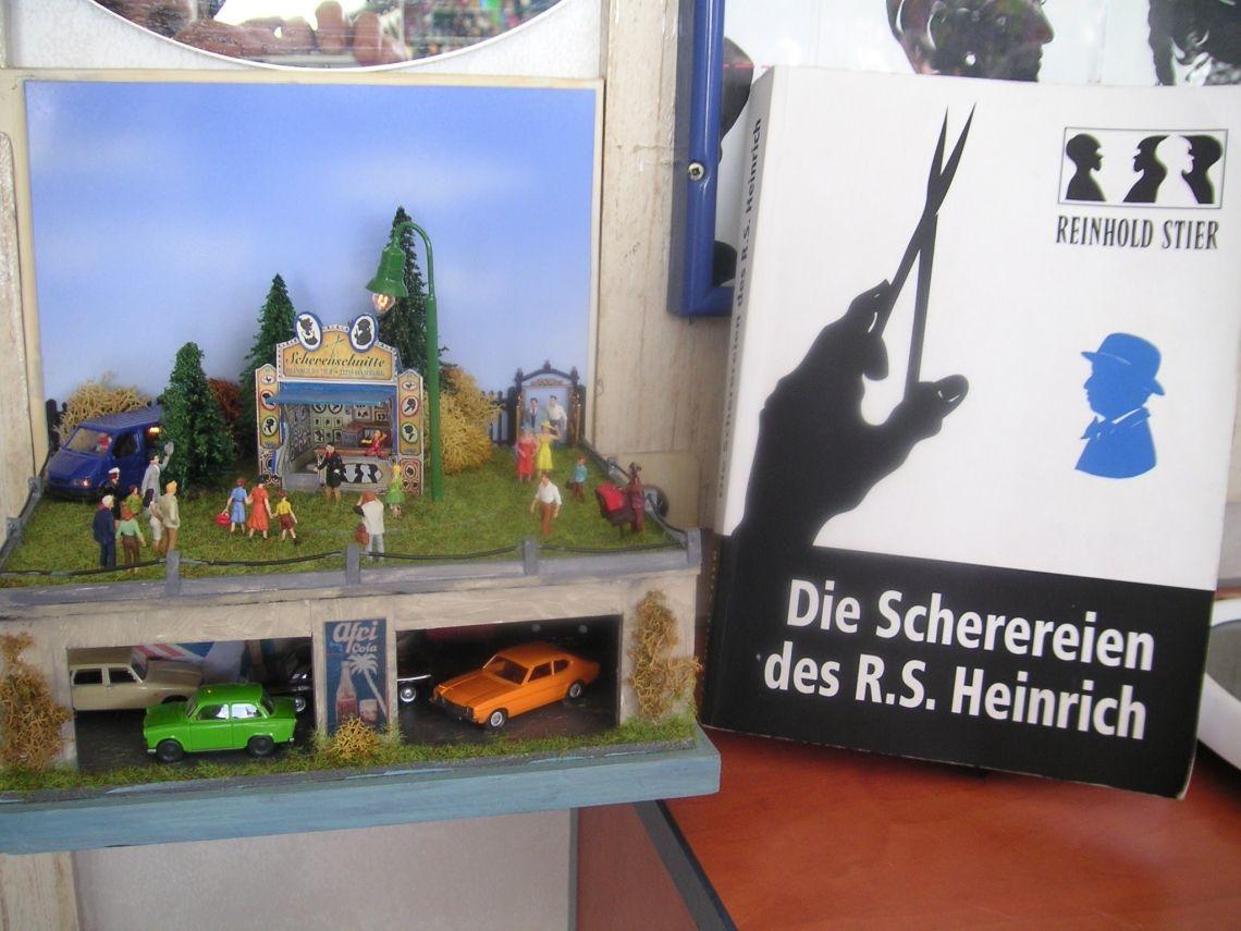 """Die Scherereien des R.S. Heinrich Das Autorenbuch des Scherenschnittkünstler """"DIE SCHEREREIEN DES R.S. HEINRICH"""" neben dem Atelier für Scherenschnitte als Miniatur."""