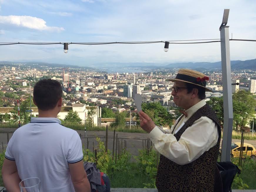 Der Scherenschnittkünstler konzentriert bei der Arbeit.  Im Hintergrund liegt Zürich bei klarem Wetter.