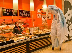 """Eine fantasievoll-tierische Atmosphäre Durch seine tierischen Verhaltensweisen wie Balzgehabe und Neugierde schafft er eine fantasievoll-tierische Atmosphäre interaktiv mit dem Publikum. Dezent sucht der scheue weiße Vogel Kontakt zum Publikum auf das er mit """"tierischen"""" Verhaltensweisen reagiert. Es entsteht feinste Situationskomik, in der Mensch und Tier zueinander finden. Enaya Dayeh erhielt den 2. Platz beim Straßenkünstlerwettbewerb 15. Mai 2011 auf der Theresienwiese in München."""