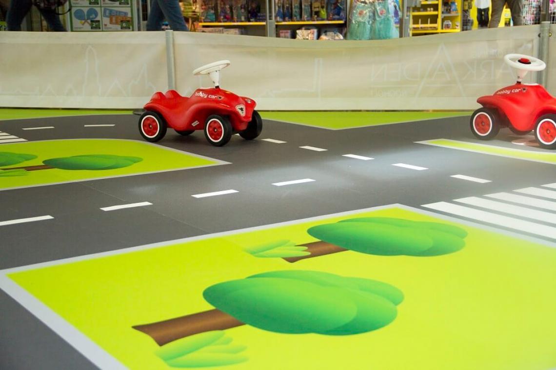 Bobby Car Rennbahn aus FOTOBODEN Shoppingcenter leben von der Frequenz. Das Center Management muss sich immer wieder neue Dinge ausdenken, wie die Frequenz und die Verweildauer der Kunden erhöht werden kann. Familien mit kleinen Kindern suchen oft nach einer Beschäftigung für die Kleinen. Fängt der Nachwuchs an zu quengeln, ist das Shoppingerlebnis schnell vorbei. Die Shopping Arkaden aus Bocholt haben sich dazu Gedanken gemacht und einfach einen kleinen Parcours für Bobby-Cars aus FOTOBODEN™ ausgelegt. Die Fahrstrecke entspricht der realen Dimension der Bobby-Cars und kann individuell von heute auf morgen auch wieder aufgenommen und in die nächste Etage umgelegt werden.  Werden auch Sie kreativ und bieten Ihren Kunden/Besuchern Abwechslung vom Alltag in Ihren Verkaufsräumen mit FOTOBODEN™