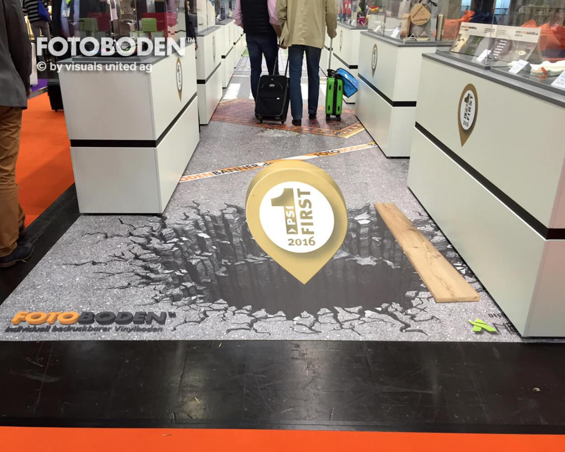 """3D Ansicht mit Fotoboden FOTOBODEN™ war erstmalig auf der PSI – der europäischen Leitmesse für Werbeartikelwirtschaft vertreten. Dabei wurde der Bereich der Produktinnovationen mit FOTOBODEN™ gestaltet. Die Bilder zeigen die 3D Ansicht des """"PSI first""""-Logos.  Ausgezeichnet wurden alle vorgestellten Innovationen, außerdem konnten die Besucher abstimmen, welches die Top-Innovation im Bereich der Werbemittel ist. FOTOBODEN™ ist nicht nur als Messeboden, sondern für viele Werbeartikel wie Z.B. Tischauflagen, Barmatten, Dartmatten und Küchenmatten das ideale Produkt. Ihrer Kreativität werden durch uns keine Grenzen gesetzt."""