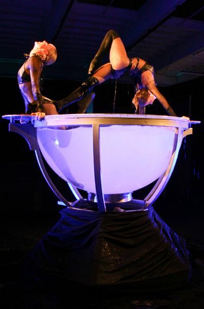 """Waterbowl, Anmut im Wasserglas Beschreibung: Das Wasserballett in einem überdimensionalen Wasserglas. Darin vollführen zwei Akrobatinnen eine kunstvoll inszenierte, anmutige Wasser-Show auf höchstem Niveau. Die fließenden Bewegungen der """"Nixen"""" verschmelzen mit dem Wasser und eine Welle der Begeisterung greift aufs Publikum über. Dank der speziell für die Show entwickelten Kostüme und der individuellen Choreographien mit abgestimmten Musik- und Lichteffekten kann der Wasserakrobatik so schnell nichts das Wasser reichen. Darüber hinaus kann die Wasserschale auch optimal als Designelement in Ihrem Szenario eingebaut werden.  Dauer des Showacts ca. 5 Min..  Leistungskatalog . ausgebildete Akrobaten und technisches Team (1-2 Personen) . Generalproben vor Ort  . Choreografie und Musikschnitt . Auf- und Abbau des Showacts . Transport (bis 500 km) . Sicherheitstechnik . Veranstalterhaftpflichtversicherung  Zusätzliche Aufwendungen vor Ort: .Übernachtung falls notwendig .Verpflegung des Teams    Preis 2.800,- pro Aktionstag   Technische Details: Durchmesser2,20 m Höhe1,66 m Gewicht200 kg / 1200 kg (befüllt) Aktionsfläche 3m x 3m Höhe Raum4,00 m Länge3,00 m Breite3,00 m Strom1 x 400 V / 63 A (32 A) WasserWasseranschluss nähe Bühne (max 20m)  Zusatzinfos: Ihre Vorteile: waterbowl ... -Erzielt höchste Aufmerksamkeit bei Ihren Gästen und Medienvertretern -Ermöglicht die spektakuläre Inszenierung Ihrer Marke und Botschaft -Ist extrem spektakulär und wird daher lange erinnert – Ihre Marke bleibt in Verbindung mit diesem Event nachhaltig verankert -Generiert kostenlose und einzigartige Berichterstattung   waterbowl eignet sich für…. -wahrnehmungsstarke Markeninszenierungen -ausgefallene Produkt-Präsentationen -außergewöhnliche Messeauftritte -Eventhöhepunkt Gala-Abenden, Firmenjubiläen und Betriebsfeiern etc.."""