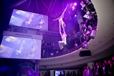 Dragon Swing (2 vertical models), völlig losgelöst von der Erde Die Artisten fliegen durch den Raum und begeistern das Publikum durch spektakuläre Luftakrobatik. Atemberaubende Überschläge, Pirouetten und Interaktionen mit Tänzern auf der Bühne sorgen für einen effektvollen Auftritt. Dabei tragen die Lufttänzer ein Spezial-Gurtzeug, das mit zwei dünnen, kaum sichtbaren Seilen verbunden ist. So kreiert Zero Gravity die Illusion der Schwerelosigkeit und bietet dem Zuschauer ein Pas de deux aus Ästhetik und Akrobatik. Für jede Zero Gravity Show wird eine eigene Choreographie entwickelt, die auf Ihre individuellen Anforderungen und Wünsche zugeschnitten ist. Angefangen bei den Kostümen über das Bühnenbild bis hin zu Gestaltung und Ablauf der Show können Sie sicher sein, ein Highlight moderner Kunst zu erhalten.  Dauer des Showacts ca. 5 Min..  Leistungskatalog: . ausgebildete Akrobaten und technisches Team (2-3 Personen) . Generalproben vor Ort  . Choreografie und Musikschnitt . Auf- und Abbau des Showacts . Transport (bis 500 km) . Sicherheitstechnik und Equipment . Veranstalterhaftpflichtversicherung  Zusätzliche Aufwendungen vor Ort: . Sound und Lichteffekte (falls notwendig) . Übernachtung falls notwendig . Verpflegung des Teams    Preis4.900,- pro Aktionstag   Technische Details: Einsatzmöglichkeitenindoor & outdoor (weltweit) Mindesthöhe ab 6,00m bis 25m  Technische Anforderungen GebäudeHängepunkte unter der Decke  AufbauzeitCa. 2h AbbauzeitCa. 1h Fahrzeug9-Sitzer Team4 - 5 Personen  Zusatzinfos:  Ihre Vorteile: Dragon Swing. . Erzielt höchste Aufmerksamkeit bei Ihren Gästen und Medienvertretern . Ermöglicht die spektakuläre Inszenierung Ihrer Marke und Botschaft . Ist extrem spektakulär und wird daher lange erinnert – Ihre Marke bleibt in Verbindung mit diesem Event nachhaltig verankert . Generiert kostenlose und einzigartige Berichterstattung   Dragon Swing eignet sich für… . wahrnehmungsstarke Markeninszenierungen . ausgefallene Produkt-Präsentationen . außerge