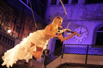 Flying Violin Während Ihres artistischen Flug-Acts spielt sie live auf der Violine – und das zum Teil sogar kopfüber. Das Licht geht an und in sanftmütiger Geschmeidigkeit erhebt sich die Artistin mit ihrer Violine am Flugwerk in die Lüfte.