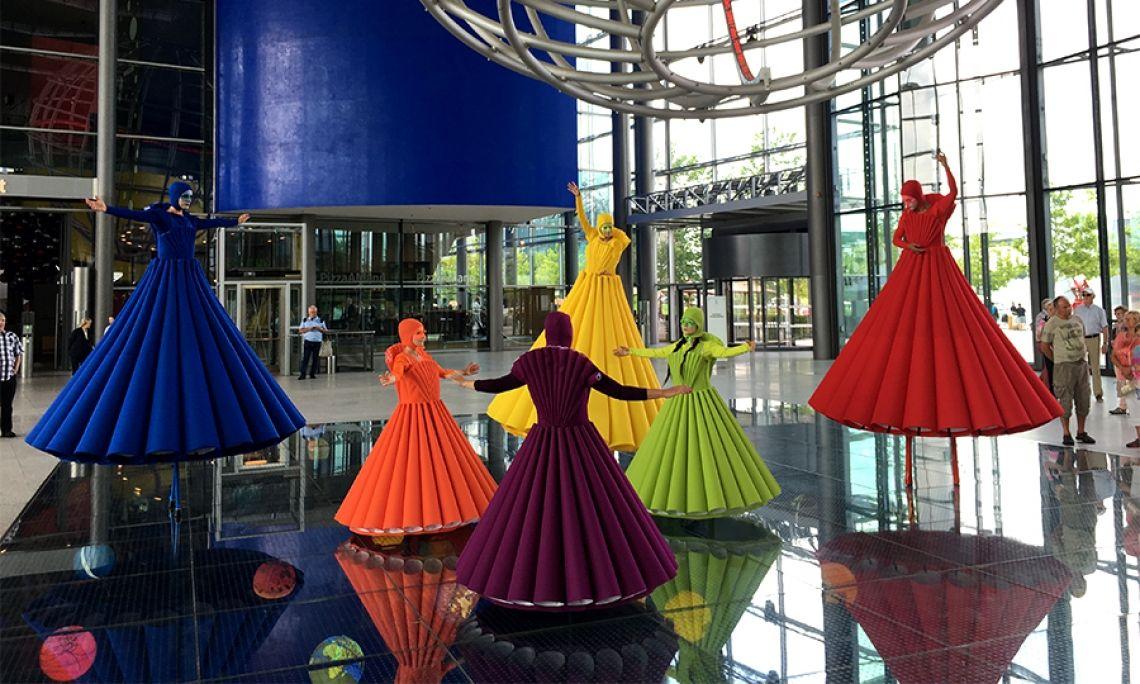 """Regenbogen Ballett Unser Regenbogen-Ballett ist ein Paraden Walk Act, angelehnt an der Idee des Triadischen Ballets. Grundlegend ist dessen dreifache Ordnung wie """"Kostüm - Bewegung - Musik"""" und """"Raum - Form - Farbe"""", aber auch die Anzahl der Boden- und Stelzenakteure mit jeweils 3. Das Publikum erwartet ein wahres Farbenspektakel."""