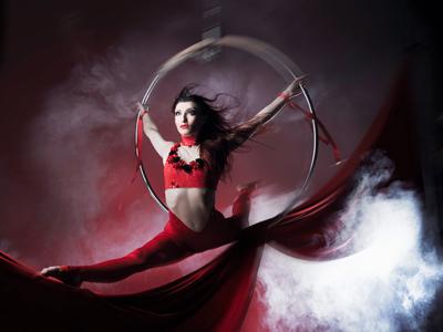 """Firebird - Olena Yakymenko Firebird - Olena Yakymenko Luftakrobatik am Ring  Feuervogel, der in den Sagen mit der Himmelsröte und der Musik in Verbindung gebracht wird, der sich verbrennt und aus der Asche wieder emporsteigt. Der einzige, der stets einzige Vogel Phönix... Einzigartig ist auch die Darbietung am Ring von Olena Yakymenko. Die Farbe des Feuers – Rot – bestimmt ihren Auftritt: Ihr Flug im Varietéhimmel ist leidenschaftlich; ihre Geschichte von Licht und Wärme, in der Sprache der Körperkunst erzählt, ist ein funkensprühender Feuerball; ihre Expression ist Glut. Das Hineinschwingen in die Innenwelt des Feuervogels wird choreographisch, musikalisch und lichttechnisch zum Ausdruck gebracht: Zu zart perlenden Klängen wird das artistische Erzählen in den weißen Spot eingetaucht – Weiß als Allegorie der Reinheit, als der Anfang aller Möglichkeiten, als Vorbereitung zu neuem kraftvollem Flügelschlag, der den Wolkenvorhang durchbrechen wird. Mit scheinbarer Leichtigkeit präsentiert die Künstlerin ästhetisch-perfekt eine Symbiose aus geschultem Körper einer Artistin und der entfachten Weiblichkeit. Absolventin der renommierten Zirkusschule in Kiew, Hauptfach Luftakrobatik, begeisterte Olena das Publikum bei den Zirkusfestivals in Großbritannien, Holland und China, sowie """"Traumtänzer- Best of Variete"""""""" TV- Festival in Kassel. Bei dem Zirkusfestival in Wiesbaden wurde sie mit dem Preis für den besten Performance ausgezeichnet. Mit ihrer Solodarbietung am Ring glänzte sie in zahlreichen Variete –, Gala- und TV-Produktionen in Europa. Im Juni 2003 bezauberte sie in Monte Carlo den Fürsten Ranier III von Monaco zu seinem 80-jährigen Jubiläum."""