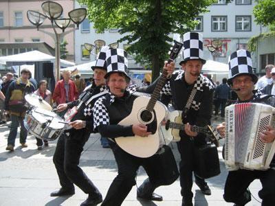 Walk Act (Marching Pop Band) 'Nomen est Omen'; bei den alten Lateinern ebenso, wie bei der Ruhrgebeats Band Walking Hats. Denn der Name der Band ist hier gleichzeitig auch eindeutig Programm – Walking. Im Gegensatz zum sonst eher üblichen konzertanten Bühnenprogramm ist hier die Bühne das Publikum oder besser gesagt – im Publikum. Die Walking Hats mischen sich nicht nur 'unter' das Volk, sie mischen es auch 'auf'!