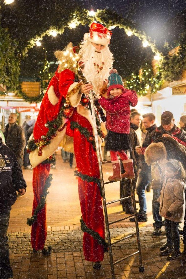 Weihnachtsriese Unser Nikolaus auf Stelzen bzw. Weihnachtsmann auf Stelzen, winterlich mit Tannengrün und LED-Lichterketten geschmückt, sorgt auf weihnachtlichen Veranstaltungen aller Art für Aufsehen. Auf Wunsch bringt der Weihnachtsriese seine Leiter mit, um den Kindern den Aufstieg zu seinem hoch gelegenen Ohr zu ermöglichen, auf daß diese ihm Weihnachtsgedichte ins Ohr flüstern oder ein Weihnachtslied zum Besten geben. Zur Belohnung darf in den Gabensack gegriffen werden.  Buchbar bis zu 4 x 20 Minuten innerhalb von 4-5 Stunden, bei Abendveranstaltungen max. 3 x 20 Minuten innerhalb von 3 Stunden. Give-aways vom Veranstalter können verteilt werden.