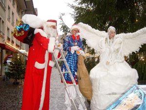 Ein großer Weißer Engel, der Süßes verschenkt, und ein Weihnachtsmann, der bezaubert